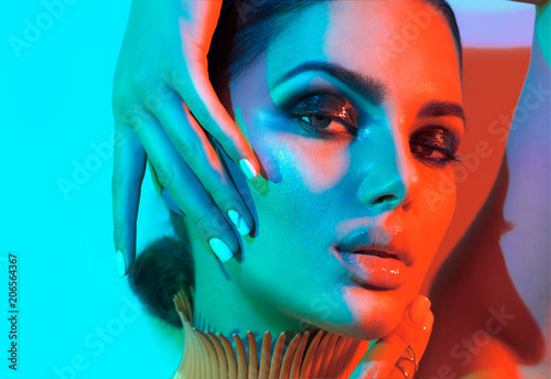 Foto op Plexiglas Beauty Fashion model woman in colorful bright lights with trendy makeup and manicure posing in studio