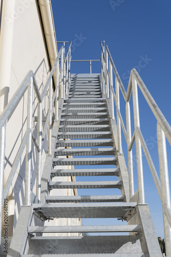 Foto op Plexiglas Trappen Metal grate staircase on the roof with railing.