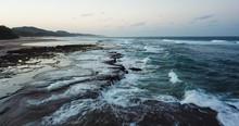 Aerial Of Waves Crashing On Reef At Sunset