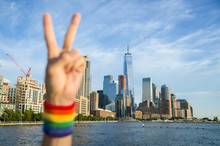 Foreground Blur Of A Defocused Hand Wearing Gay Pride Rainbow Sweat Band Making Peace Sign In Front Of City Skyline. Focus On Buildings In Backgrounds.