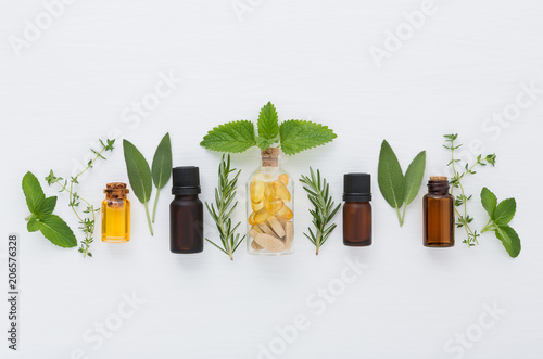 Poster Condiments Bottle of essential oil and herbal medicine with fresh herbs sage, rosemary, thyme, mint, lemon balm and spearmint setup with flat lay on white wooden table. top view