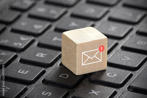 Fotografía  New email graphic on wooden block over laptop keyboard