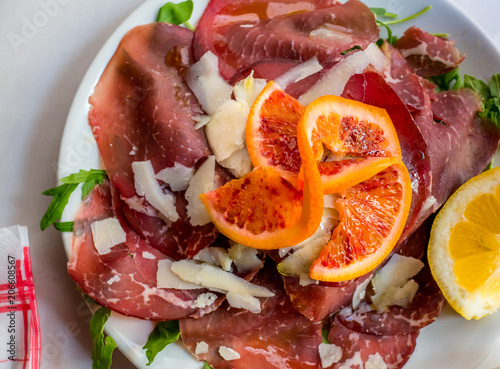 Slices of Bresaola itaian meat with parmesan, orange and lemon.