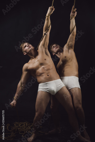 two gymnastic acrobatic caucasian men twins in same pose. Canvas Print