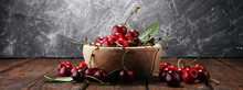 Cherry. Red Fresh Cherries In Bowl And A Bunch Of Cherries On The Table