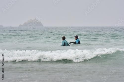 Un couple de seniors pratique le longe côte sur une plage de Bretagne