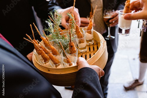 Photo Tasty wedding appetizers served by waiters to the guests