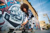 Fototapeta Młodzieżowe - African American girl stands on skateboard with wall on background