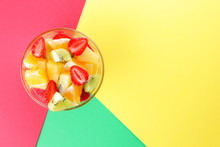 Fruit Salad From Pineapple, Kiwi, Orange, Strawberry. Multicolored Sliced Fruit In A Transparent Dish. Vegetarian Food On A Multi-colored Pop Art Background. Copy Space.
