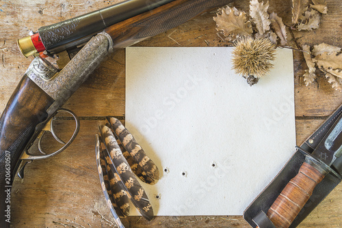 Garden Poster Hunting Hunting season concept: beautiful hunting gun with cartridges, knife, paper on old wooden background