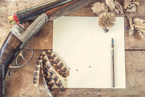 Foto op Canvas Jacht Hunting concept: hunting rifle, target upsite down, pheasant feathers on old wooden background top view