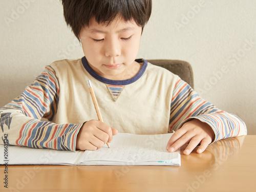 自宅で算数の宿題をする小学生の男の子