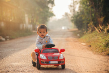 Little Boy Driving Big Toy Car ,Child Enjoying Warm Summer Day In Sunrise Morning