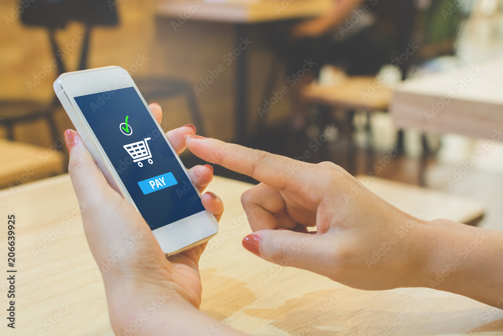 Fototapeta Concept online payment mobile technology. Hand of female using smartphone touching pay button mobile banking application in restaurant