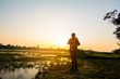 Hipster young man with backpack enjoying sunset on . Tourist traveler on background grass. Hiker looking sunlight in trip in thailand country, copy space