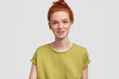 Studio shot of pleasant looking thoughtful redhead female in casual green t shirt, has charming smile, feels relaxed and joyful, isolated on white background. People, facial expressions concept