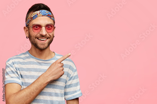 Платно Horizontal shot of pleasant looking young hippy male with stubble, wears stylish pink sunglasses and headband, indicates at upper right corner, poses in studio