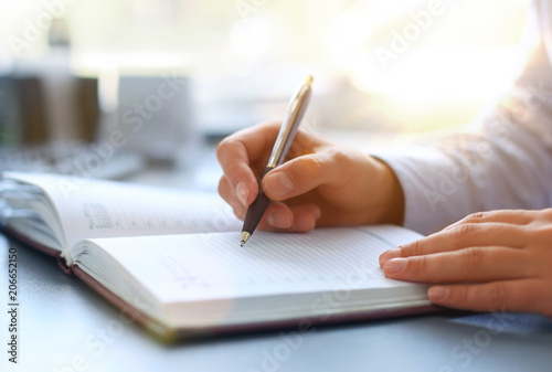 Businesswoman makes a note in notebook. Canvas Print