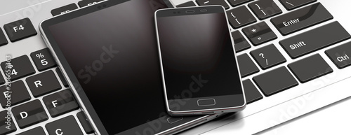 Photo Smartphone and tablet with blank black screens on computer keyboard