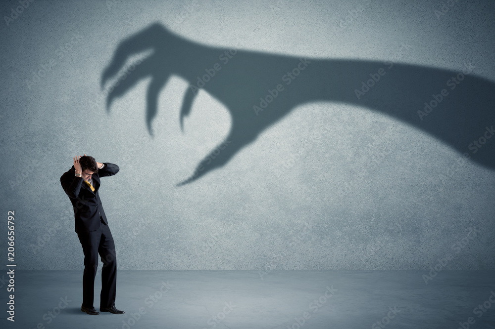 Fototapeta Business person afraid of a big monster claw shadow concept on background