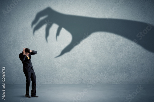 Fotografiet Business person afraid of a big monster claw shadow concept on background