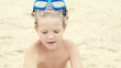 Little curly Caucasian boy with snorkeling equipment sitting on sand on tropical beach.