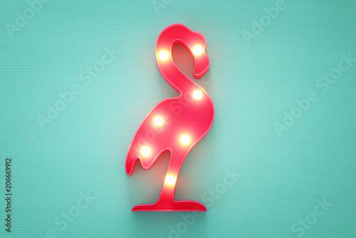Obraz na plátně a plastic flamingo lamp with leds over mint wooden background