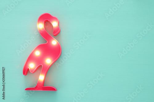 Fotografie, Obraz  a plastic flamingo lamp with leds over mint wooden background