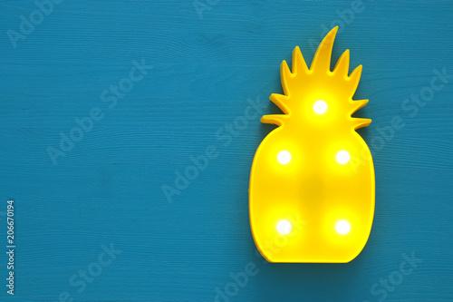 Obraz na plátně  a plastic pineapple lamp with leds over blue wooden background