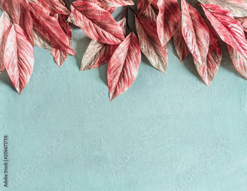 Fotografia  Beautiful pink leaves border on pastel blue background , top view, flat lay