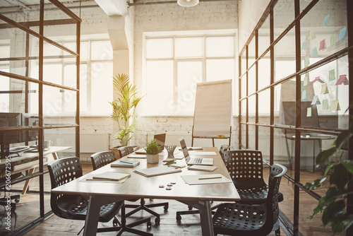 Obraz Modern digital devices with books and papers situating on wooden desk. Chairs and whiteboard are near it in modern office - fototapety do salonu