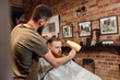 Barber and bearded man in barber shop