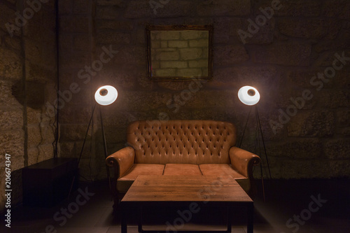 Leather Sofa Lamps And Table In Dark Interior Stone Wall On Background Brutal Atmosphere