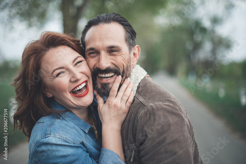 We are happy together. Joyful husband and wife are bonding to each other with fondness. They are looking at camera and laughing while standing on path outdoor