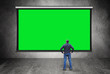 canvas print picture - Man stands in front of big empty green screen