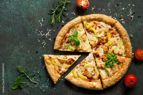 Pizza menu. Delicious traditional Italian pizza Hawaiian on on a dark stone or concrete background. Top view, copy space.
