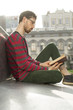 A modern young man is reading a book in an urban setting. A student is sitting on the street near the university.