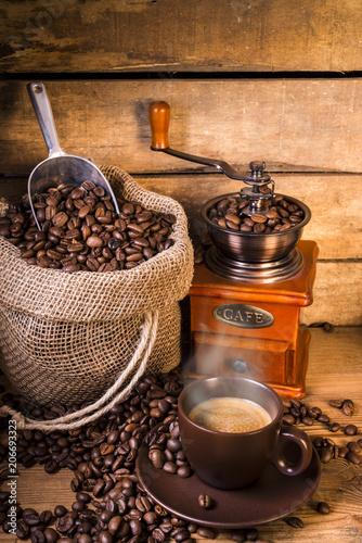 Keuken foto achterwand Koffiebonen chicchi di caffè in sacco di iuta con macinino di legno e tazzina di caffè fumante