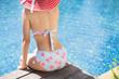 Woman is sitting she wears a bikini relaxing in the summer, she is in the pool.