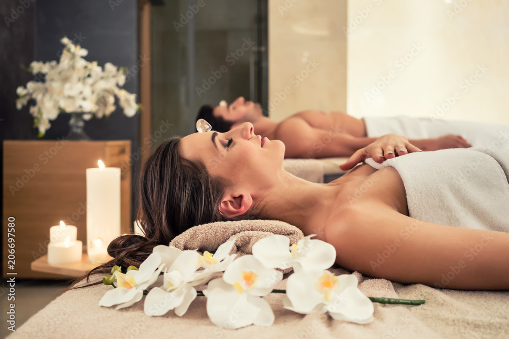 Fototapeta Young man relaxing with his partner on massage beds at modern spa and wellness center