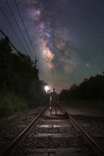 Man Walking On Train Tracks To...