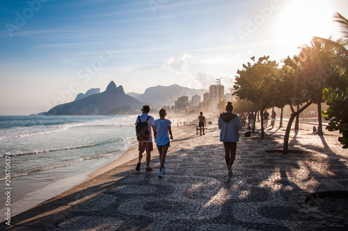People walk on the famous sidewalk of Ipanema beach by sunset