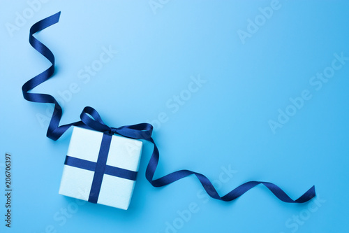 Gift box with curly satin ribbon on blue pastel background. Top view. Copy space.