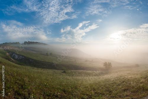 Spoed Foto op Canvas Blauwe hemel Fog in valley and over hills