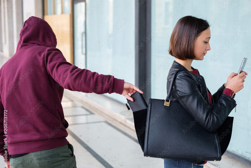 Fototapeta Thief picking the wallet from the bag of a careless girl