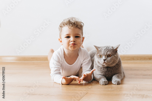 Obraz adorable toddler boy and grey british shorthair cat lying on floor together at home - fototapety do salonu