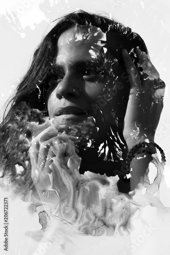 Paintography. Double Exposure portrait of a seductive ethnic woman with nose piercing and strong expression combined with hand drawn watercolor painting. black and white