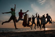 Silhouettes of group of people in a jump at sunset. nine young men and women depicted in a jump against the evening sky and the beach. Friends and holiday concept
