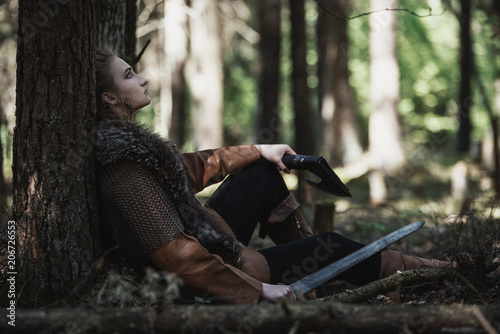 Photo  Viking woman with sword wearing traditional warrior clothes in a deep mysterious forest