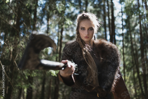 Plakát  Viking woman with hammer wearing traditional warrior clothes in a deep mysterious forest